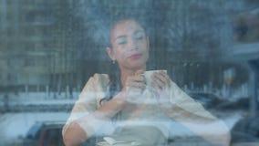 Ονειροπόλος νέα γυναίκα με ένα φλυτζάνι του τσαγιού σε μια ζωή πόλεων προσοχής καφέδων απόθεμα βίντεο