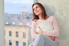 Ονειροπόλος νέα γυναίκα που αγκαλιάζει το μαξιλάρι της το πρωί και το looki στοκ φωτογραφία