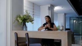 Ονειροπόλος νέα γυναίκα που απολαμβάνει τον καφέ της σε έναν καφέ απόθεμα βίντεο