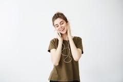 Ονειροπόλος νέα όμορφη μουσική ακούσματος χαμόγελου κοριτσιών στα ακουστικά πέρα από το άσπρο υπόβαθρο Στοκ Εικόνες