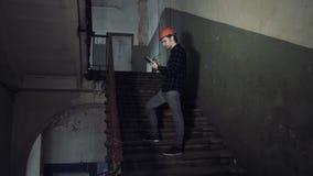 Ονειροπόλος χαμογελώντας επισκευαστής που κρατά την ταμπλέτα στο παλαιό κτήριο απόθεμα βίντεο