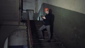 Ονειροπόλος χαμογελώντας επισκευαστής που κρατά την ταμπλέτα στο παλαιό κτήριο φιλμ μικρού μήκους