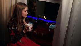Ονειροπόλος όμορφη γυναίκα που απολαμβάνει το φλιτζάνι του καφέ φιλμ μικρού μήκους
