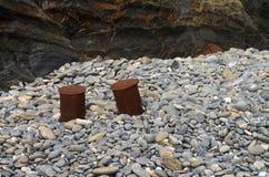 Οξυδωμένες δένοντας σφήνες που χρησιμοποιούνται ως σκαμνιά στις πέτρες παραλιών Στοκ Φωτογραφία