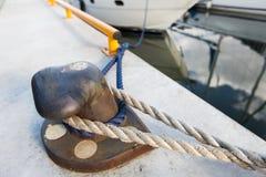 Οξυδωμένος στυλίσκος πρόσδεσης σιδήρου με το σχοινί στην αποβάθρα Στοκ φωτογραφία με δικαίωμα ελεύθερης χρήσης