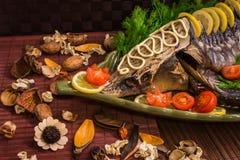 Οξύρρυγχος που διακοσμείται με το λεμόνι και τις ντομάτες σε ένα πράσινο πιάτο Στοκ Εικόνες