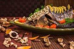 Οξύρρυγχος που διακοσμείται με το λεμόνι και τις ντομάτες σε ένα πράσινο πιάτο Στοκ Εικόνα