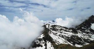 Οπίσθια εναέρια τοπ άποψη πέρα από το νεφελώδες δύσκολο χιονώδες βουνό στην ηλιόλουστη ημέρα με τα σύννεφα Ιταλικά βουνά ορών το  φιλμ μικρού μήκους