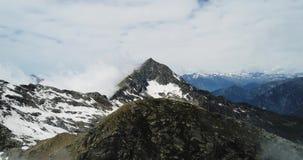 Οπίσθια εναέρια τοπ άποψη πέρα από το νεφελώδες δύσκολο χιονώδες βουνό στην ηλιόλουστη ημέρα με τα σύννεφα Ιταλικά βουνά ορών το  απόθεμα βίντεο