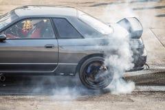 Οπίσθια καίγοντας ρόδα σπορ αυτοκίνητο κίνησης ροδών για την προθέρμανση πριν από την έναρξη ανταγωνισμού Στοκ Εικόνες