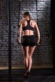 Οπίσθια φωτογραφία της νέας φίλαθλης άσκησης γυναικών με τα γυμναστικά δαχτυλίδια στη γυμναστική crossfit Στοκ φωτογραφία με δικαίωμα ελεύθερης χρήσης