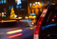 Οπίσθια φω'τα ενός μαύρου αυτοκινήτου, πόλη βραδιού κινηματογραφήσεων σε πρώτο πλάνο στοκ φωτογραφία με δικαίωμα ελεύθερης χρήσης
