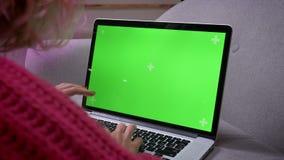 Οπίσθιος πυροβολισμός κινηματογραφήσεων σε πρώτο πλάνο των θηλυκών χεριών που δακτυλογραφούν στο lap-top με τη μεγάλη συγκέντρωση φιλμ μικρού μήκους