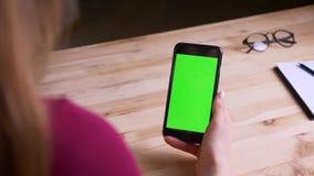 Οπίσθιος πυροβολισμός της επιχειρηματία που μιλά στο videochat στο smartphone με την πράσινη οθόνη χρώματος στην αρχή απόθεμα βίντεο