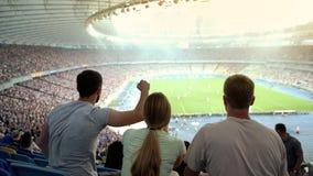 Οπαδοί ποδοσφαίρου που υποστηρίζουν την αγαπημένη ομάδα στο στάδιο, ενθαρρυντικό για τη νίκη, αντιστοιχία στοκ φωτογραφίες