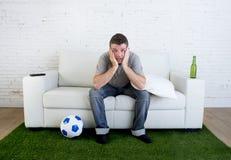 Οπαδός ποδοσφαίρου που προσέχει τον αγώνα TV στον καναπέ με τον τάπητα ι πισσών χλόης Στοκ Φωτογραφία