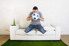 Οπαδός ποδοσφαίρου που προσέχει τον αγώνα TV στον καναπέ με τον τάπητα ι πισσών χλόης Στοκ φωτογραφία με δικαίωμα ελεύθερης χρήσης