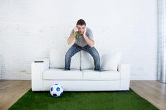 Οπαδός ποδοσφαίρου που προσέχει τον αγώνα TV στον καναπέ με τον τάπητα ι πισσών χλόης Στοκ Εικόνες