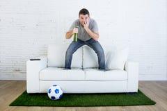 Οπαδός ποδοσφαίρου που προσέχει τον αγώνα TV στον καναπέ με τον τάπητα πισσών χλόης στην πίεση Στοκ Φωτογραφίες