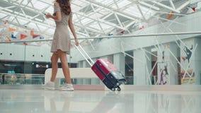 Οπισθοσκόπος γυναίκα με τις αποσκευές που περπατά προς το ιδιωτικό αεριωθούμενο αεροπλάνο στον τελικό, ευτυχή τουρίστα σπουδαστών απόθεμα βίντεο