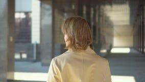 Οπισθοσκόπος γυναίκα που περπατά μέσω της οδού Η γυναίκα με την όμορφη άσπρη τρίχα και τα άσπρα δόντια o απόθεμα βίντεο