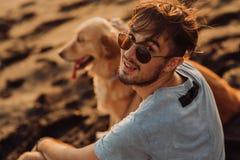 Οπισθοσκόπος ενός ατόμου και μιας χρυσής συνεδρίασης σκυλιών στην παραλία στοκ εικόνες