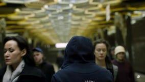 Οπισθοσκόπος ενός ατόμου με ένα σκούρο μπλε hoodie στο περπάτημα μέσω του πλήθους στο σταθμό, έννοια αντίστασης Κλείστε επάνω για φιλμ μικρού μήκους