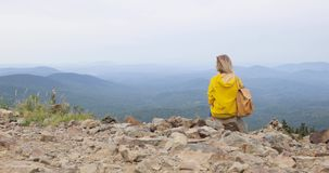 Οπισθοσκόπος ενός κοριτσιού πάνω από ένα βουνό, έννοια του τουρισμού απόθεμα βίντεο