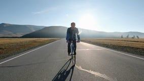 Οπισθοσκόπος ενός νεαρού άνδρα με το ποδήλατο στο υπόβαθρο θερινής φύσης υγιής τρόπος ζωής έννοιας η δεκαετία του '20 4k φιλμ μικρού μήκους