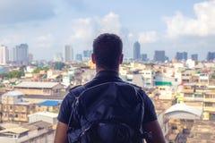 Οπισθοσκόπος ενός backpacker που εξετάζει την πόλη από τη στέγη του buildi στοκ φωτογραφία