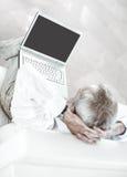 Οπισθοσκόπος επιχειρηματίας με μια ανοικτή συνεδρίαση lap-top στον καναπέ στο σύγχρονο γραφείο Στοκ φωτογραφία με δικαίωμα ελεύθερης χρήσης