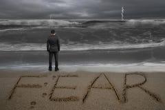 Οπισθοσκόπος επιχειρηματίας που στέκεται αντιμετωπίζοντας τη λέξη φόβου στην παραλία άμμου Στοκ Εικόνες