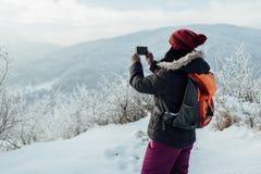 Οπισθοσκόπος μιας γυναίκας έντυσε τις θερμές παίρνοντας εικόνες των χιονωδών λόφων Στοκ Φωτογραφία