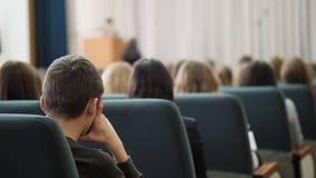 Οπισθοσκόπος μιας τρυπημένης συνεδρίασης ακροατών στην αίθουσα και του ακούσματος στον ομιλητή απόθεμα βίντεο