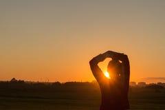 Οπισθοσκόπος σκιαγραφία του νέου θηλυκού που στέκεται με τα χέρια πίσω από επικεφαλής και που εξετάζει το ηλιοβασίλεμα στοκ φωτογραφία
