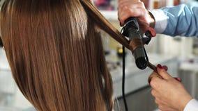 Οπισθοσκόπος στενός επάνω μιας γυναίκας που παίρνει την τρίχα της κατσαρωμένη από ένα επαγγελματικό hairstylist φιλμ μικρού μήκους