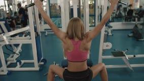 Οπισθοσκόπος στην αθλητική ξανθή φίλαθλο που θερμαίνει την πίσω αντλώντας το σίδηρο στο σταθμό ικανότητας 4K απόθεμα βίντεο