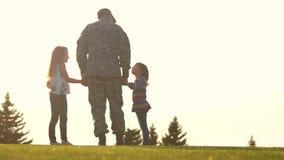 Οπισθοσκόπος στρατιωτικός στο camoubackgrounde με τα παιδιά φιλμ μικρού μήκους