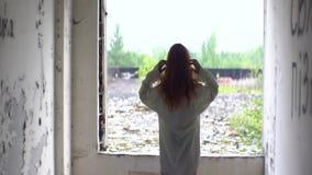 Οπισθοσκόπος της άγνωστης τρελλής κόκκινης επικεφαλής γυναίκας στο άσπρο πουκάμισο που κοιτάζει μέσω του παραθύρου στο εγκαταλειμ απόθεμα βίντεο