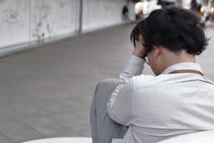 Οπισθοσκόπος της ανήσυχης καταπονημένης νέας ασιατικής συνεδρίασης επιχειρησιακών ατόμων και σχετικά με το μέτωπο με τα χέρια στοκ φωτογραφία με δικαίωμα ελεύθερης χρήσης