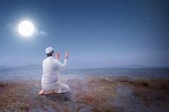 Οπισθοσκόπος της ασιατικής μουσουλμανικής συνεδρίασης ατόμων προσεηθείτε μέσα τη θέση ενώ αυξημένα χέρια και επίκληση στον αμμόλο στοκ εικόνα με δικαίωμα ελεύθερης χρήσης