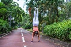 Οπισθοσκόπος της ικανότητας η γυναίκα που κάνει handstand την άσκηση που στέκεται κατευθείαν η πάροδος πάρκων όπλων το καλοκαίρι Στοκ Εικόνες