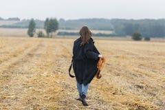 Οπισθοσκόπος της καυκάσιας γυναίκας brunette στο μαύρο παλτό που περπατά στον τομέα στοκ εικόνες