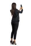 Οπισθοσκόπος της μακρυμάλλους εταιρικής γυναίκας στο κοστούμι που παίρνει τη φωτογραφία με το κινητό τηλέφωνο Στοκ φωτογραφίες με δικαίωμα ελεύθερης χρήσης