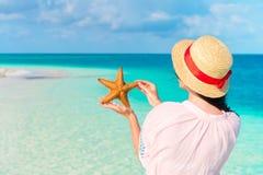 Οπισθοσκόπος της νέας γυναίκας με τον αστερία στην άσπρη παραλία στην επιφύλαξη φύσης στοκ φωτογραφία