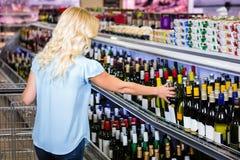 Οπισθοσκόπος της ξανθής γυναίκας που παίρνει το μπουκάλι κρασιού στοκ εικόνα