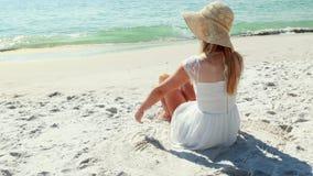 Οπισθοσκόπος της ξανθής συνεδρίασης γυναικών στην παραλία και της εξέτασης τον ωκεανό απόθεμα βίντεο