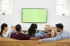 Οπισθοσκόπος της ομάδας νέων φίλων που προσέχουν την τηλεόραση από κοινού Στοκ εικόνα με δικαίωμα ελεύθερης χρήσης