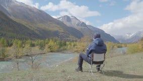 Οπισθοσκόπος της συνεδρίασης τύπων σε μια όχθη ποταμού στην κοιλάδα και τη μελέτη mountans 4k φιλμ μικρού μήκους