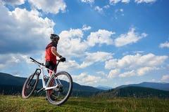 Οπισθοσκόπος του αθλητικού ποδηλάτη αθλητικών τύπων sportswear και του κράνους που στέκεται με το διαγώνιο ποδήλατο χωρών στοκ φωτογραφίες με δικαίωμα ελεύθερης χρήσης